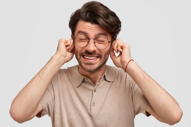 不機嫌な男の写真は不満で耳を塞ぎ、誰かを無視する