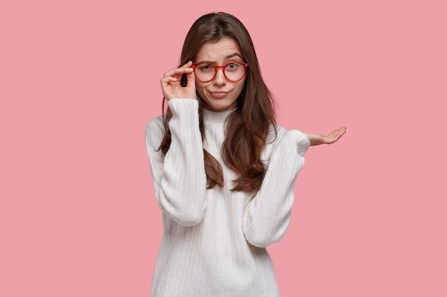 불쾌한 진지한 젊은 아가씨의 사진은 안경을 통해 꼼꼼하게 보이고, 손바닥을 들어 올리고, 대형 점퍼를 착용합니다.