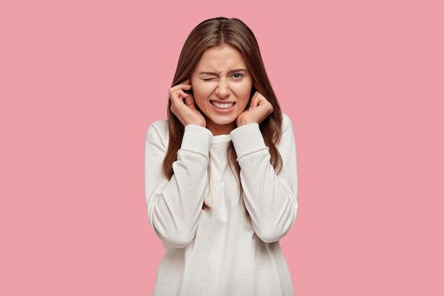 不機嫌な女性の写真は不満で耳を塞ぎ、迷惑な音や騒音を聞きたくない