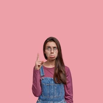 어두운 긴 머리를 가진 불쾌한 여성의 사진, 나쁜 소식으로 스트레스를 받고, 광학 안경과 데님 바지를 착용