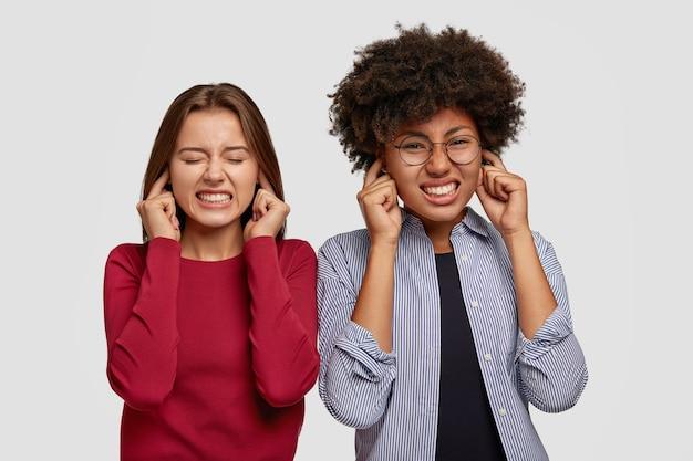 不機嫌な女性の写真は耳を塞ぐ