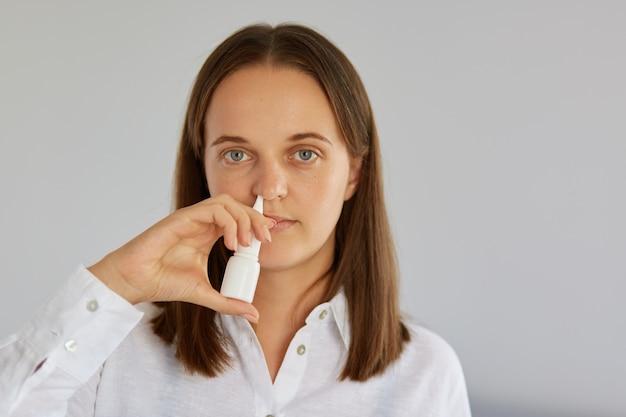 Фотография неудовлетворенной темноволосой женщины, которая пользуется спреем для носа, страдает заложенным носом, носит белую одежду, позирует в помещении на фоне светлой стены, смотрит в камеру.