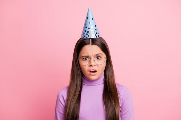 Фотография неудовлетворенной маленькой девочки чувствует себя впечатленной носить фиолетовый джемпер, изолированный на пастельном цветном фоне