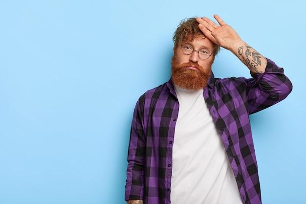 Фото недовольного стильного рыжего парня, позирующего на фоне синей стены