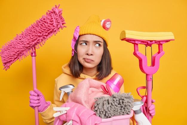 Фотография недовольной женщины, сосредоточенно нахмурившаяся, занимающаяся уборкой, держит швабры для мытья пола, собирающейся стирать, на желтой стене