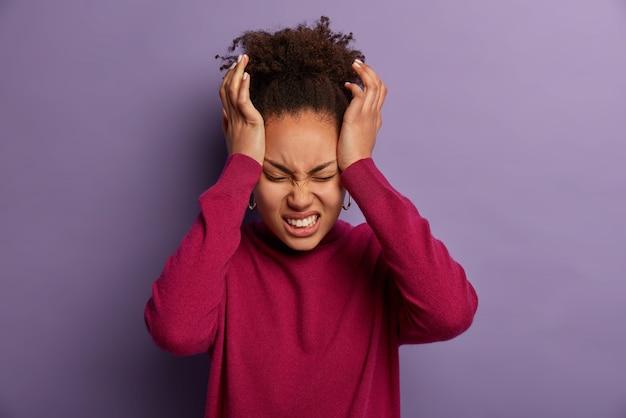 불만족스러운 여성의 사진은 사원에 손을 대고 견딜 수없는 두통을 앓고 있으며 고통으로 치아를 움켜 쥐고 퇴근 후 지친 상태이며 보라색 벽에 고립 된 부르고뉴 터틀넥을 착용합니다.