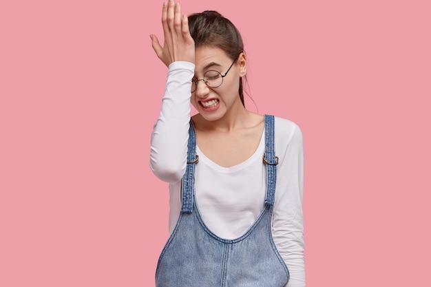 불만족 한 젊은 여성의 사진은 잘못된 일을 후회하고 이마에 손을 대고 치아를 움켜 쥐고 있습니다.