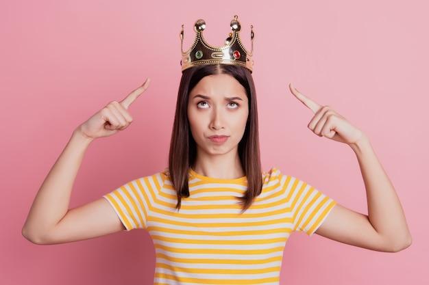 의심스러운 의아해하는 버릇없는 자기 중심적인 여성의 사진은 분홍색 배경에 손가락 왕관이 올려져 있음을 나타냅니다.