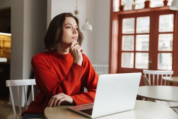 レストランでノートブックを使用しながら、セーターをよそ見で20代の夢を見る若い女性の写真