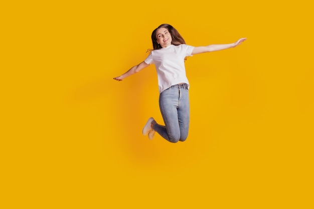 Фотография мечтательной беззаботной дамы прыгает, наслаждаясь выходными, весело носить белую футболку, позирующую на желтом фоне