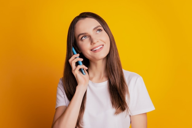 夢のようなインスピレーションを得た女性の写真は、電話の話を保持します空のスペースを見て黄色の背景にポーズをとって白いtシャツを着ます
