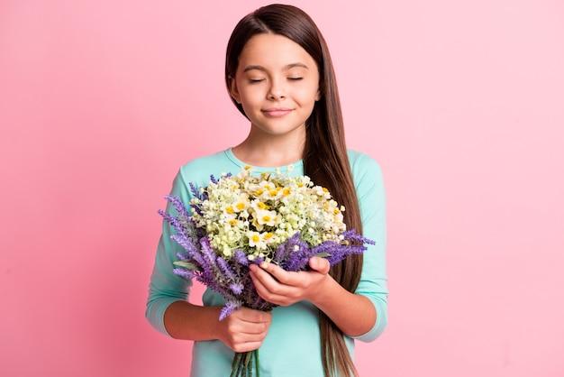 꿈꾸는 듯한 아름다운 작은 히스패닉 여성의 긴 머리 손이 꽃다발을 들고 신선한 여름 꽃 눈을 감고 상상을 하고 청록색 운동복을 입고 분홍색 배경을 격리하는 사진