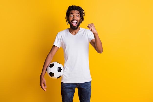 Фотография восторженного темнокожего парня, держащего мяч в матче команды поддержки, в повседневной футболке, джинсах, изолированном на желтом фоне