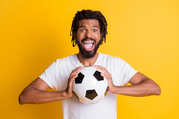 Фотография восторженного темнокожего парня, держащего кожаный мяч, часы матча, крик, цель, носить повседневную футболку, изолированный желтый цвет фона