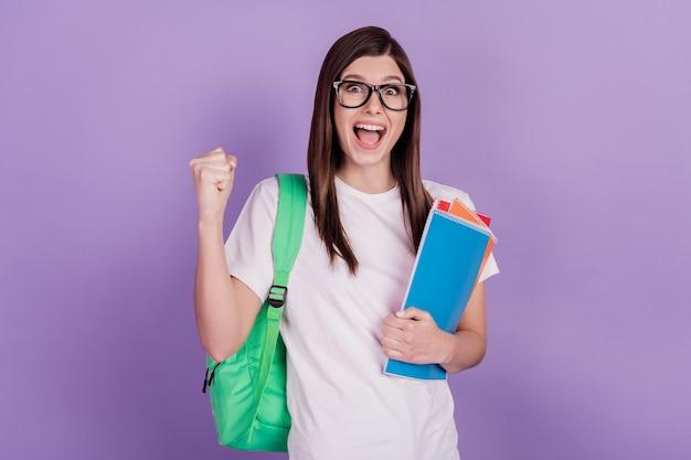 황홀한 학생 소녀의 사진은 카피북 가방을 들고 주먹을 들고 고립된 보라색 배경을 이깁니다.
