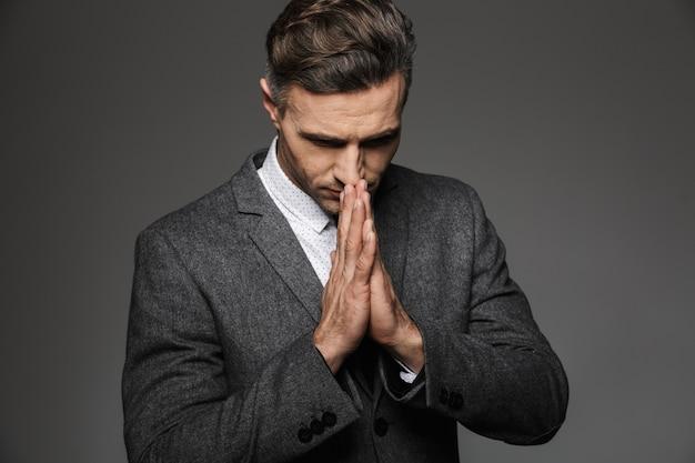 Фото элегантного концентрированного человека в классическом костюме, держащего ладони вместе для молитвы, изолированного над серой стеной