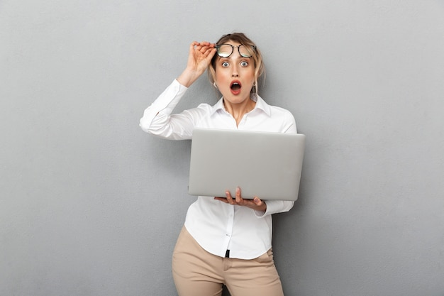孤立した、オフィスで立ってラップトップを保持している眼鏡をかけている感情的な実業家の写真