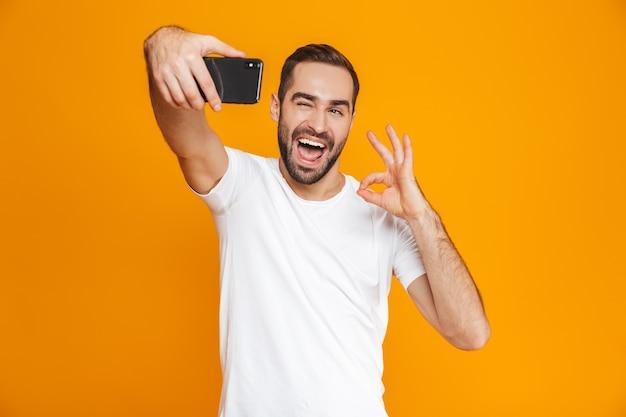 Фотография эмоционального парня 30-х годов в повседневной одежде, смеющегося и делающего селфи на мобильном телефоне, изолирована