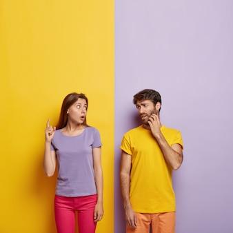 Фотография эмоционально впечатленной женщины пытается что-то объяснить мужчине, указывает на шок наверху, недовольный парень царапает щетину, носит желтую футболку