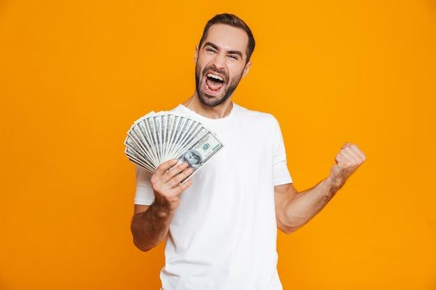 Фотография эмоционального мужчины 30-х годов в повседневной одежде, держащего кучу денег, изолированные