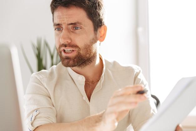 Фотография эмоционального офисного работника 30-х годов в белой рубашке, использующего ноутбук и бумажные документы, сидя за столом на современном рабочем месте