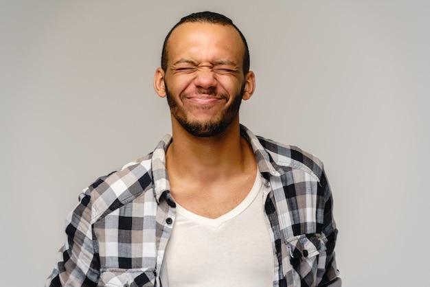 Фото эмоционального молодого афро-американского человека с закрытыми глазами, стоя на сером.