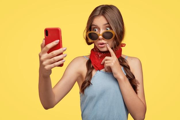 감동적인 놀란 여성의 사진은 선글라스를 통해 놀라움으로 보이고, 현대적인 휴대 전화를 들고, 자신의 사진을 찍고, 새로운 모습으로 충격을 받고, 목에 빨간 두건을 착용합니다.