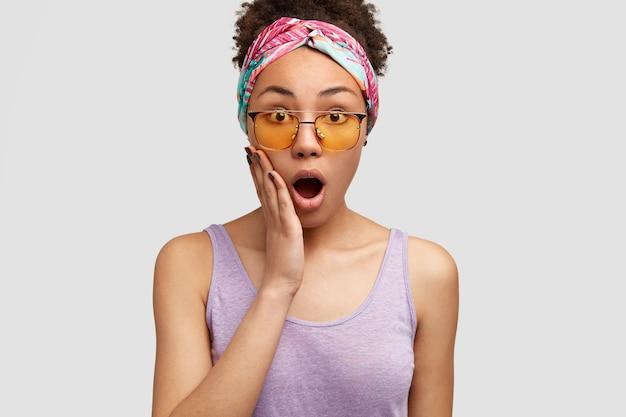 感動的な驚きのアフリカ系アメリカ人女性の写真は、口を大きく開き、手のひらを頬に保ち、スタイリッシュなヘッドバンドと紫色のベストを着て、白い壁に隔離されています。人と感情の概念