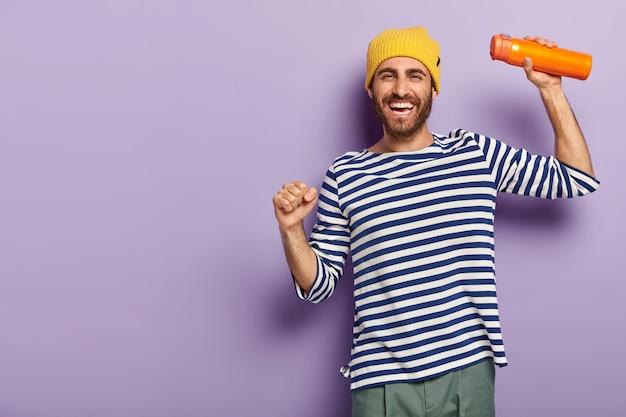활력이 넘치는 쾌활한 남자 관광의 사진은 유행의 옷을 입고 장난스럽게 춤을 추고, 보온병을 운반하고, 기꺼이 미소를 짓고, 보라색 배경 위에 고립 된 행복한 분위기를 가지고 있습니다.