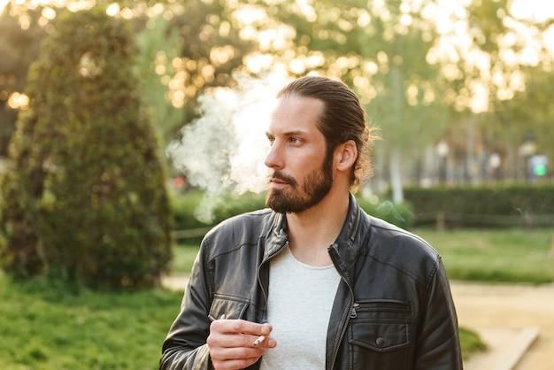 Фотография европейского красивого мужчины в белой футболке, смотрящего в сторону и курящего сигарету, во время прогулки в зеленом парке
