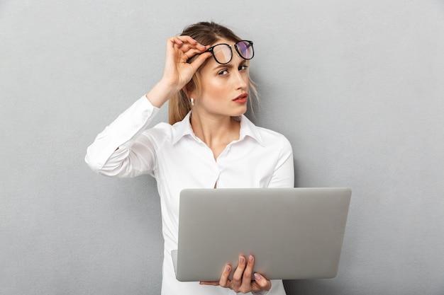 眼鏡をかけて立って、オフィスでラップトップを保持しているヨーロッパの実業家の写真、分離