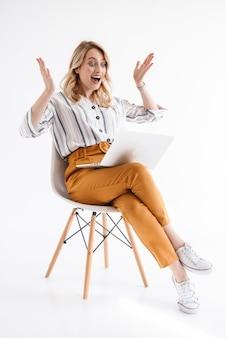 Фотография европейской возбужденной женщины в повседневной одежде, смотрящей на ноутбук, сидя в кресле, изолированной над белой стеной
