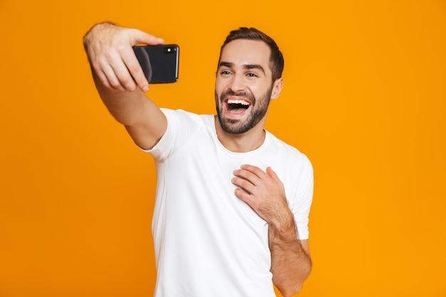 Фотография европейского парня 30-х годов в повседневной одежде, смеющегося и делающего селфи на мобильном телефоне, изолирована