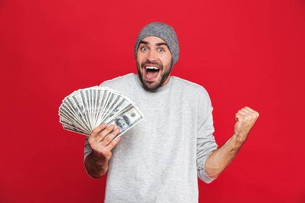 Фотография европейского парня 30-х годов в повседневной одежде, радующегося и держащего наличные деньги изолированными