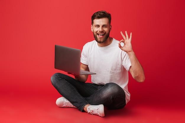 Tシャツとジーンズが足を組んで床に座って、赤い背景に分離されたラップトップを押しながらokサインを示すヨーロッパのうれしそうな男の写真