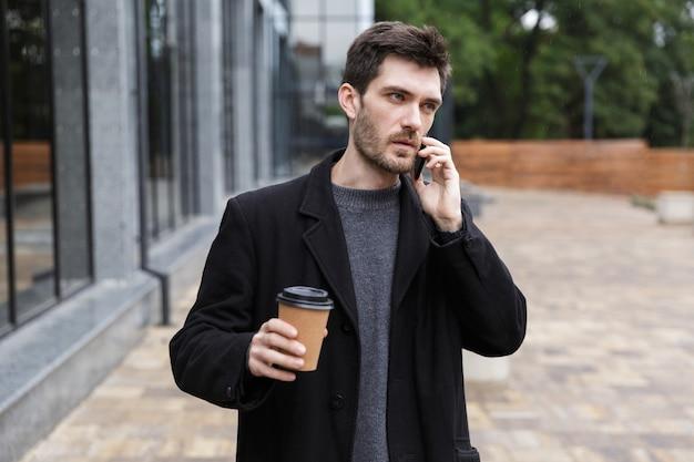 테이크 아웃 커피와 함께 야외 산책을하는 동안 휴대 전화를 사용하는 유럽 남성 20 대 사진