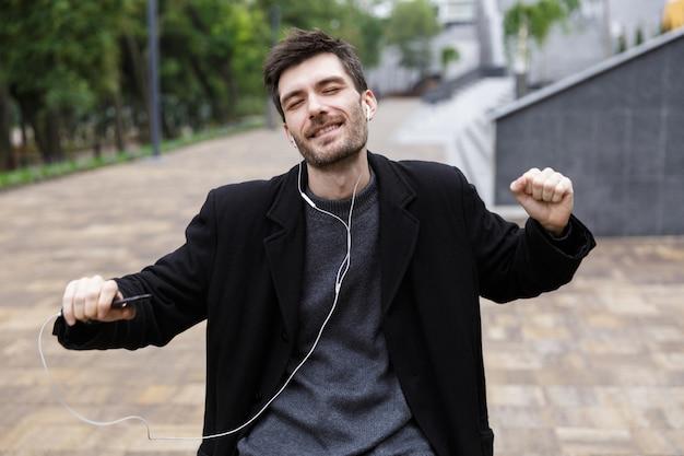 야외를 걷는 동안 휴대 전화를 사용하여 이어폰을 착용하고 춤을 추는 유럽 남성 20 대 사진