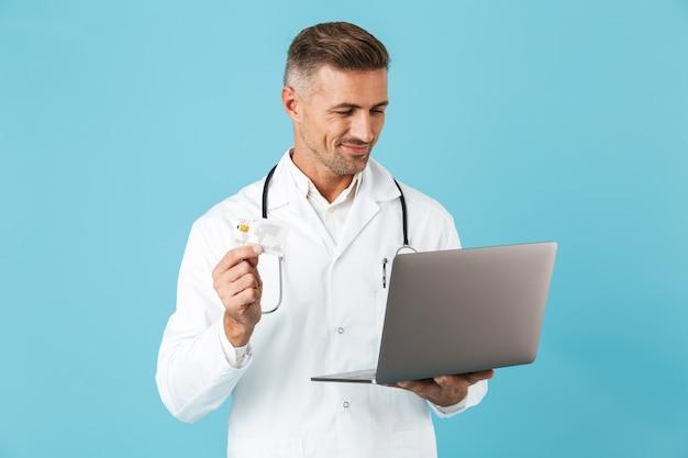 青い壁の上に孤立して立って、ラップトップとクレジットカードを保持している白い医療コートと聴診器を身に着けているヨーロッパ人の写真