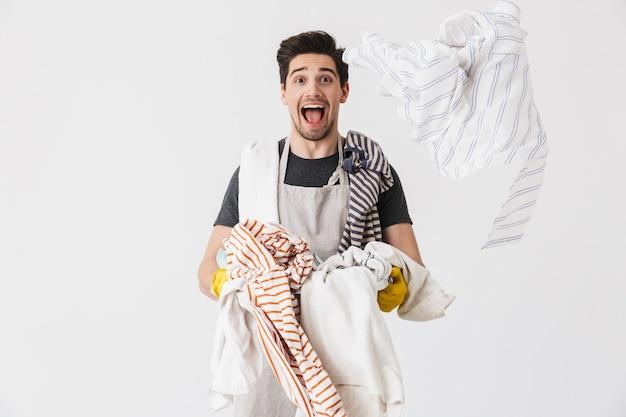 白で隔離の服と洗濯かごを運んで笑っている黄色のゴム手袋を着用してヨーロッパの若い男の写真