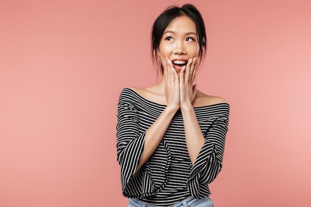 기본 옷을 입은 흥분한 아시아 여성의 사진이 웃고 있고 붉은 벽에 고립된 그녀의 얼굴을 덮고 있습니다