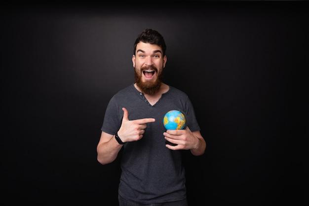 Фотография возбужденного бородатого парня, указывающего на маленький глобус на темном изолированном фоне