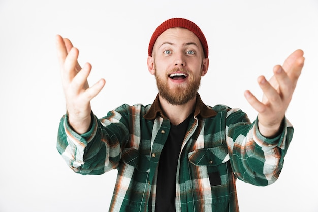 Фото возбужденного бородатого парня в шляпе и клетчатой рубашке, жестикулирующего, стоя изолированно на белом фоне