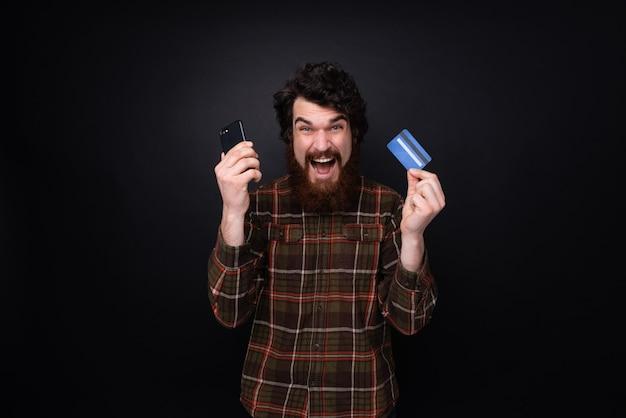 어두운 배경 위에 서 있는 손에 신용 카드와 스마트폰을 들고 흥분한 수염 난 남자의 사진