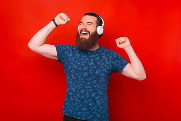 무선 헤드폰으로 축하하고 음악을 듣는 흥분된 수염 난 힙스터 남자의 사진