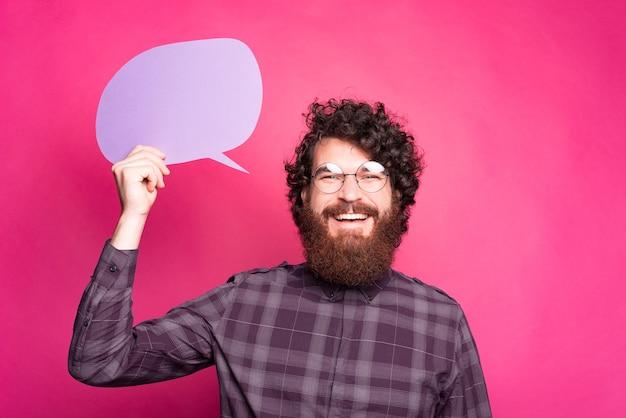 ピンクの背景の上に空の吹き出しを保持し、笑顔で興奮しているひげを生やした流行に敏感な男の写真