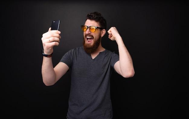 Фотография возбужденного бородатого мужчины, держащего мобильный телефон, качающегося и празднующего с поднятыми руками