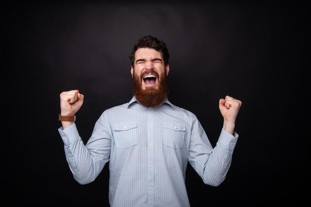 Фотография возбужденного бородатого парня кричать с закрытыми глазами и праздновать с поднятыми руками, стоя на темном фоне изолированные