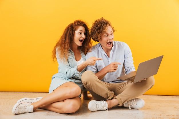 黄色の背景で隔離、床に座って銀のラップトップを使用して興奮した白人カップルの男性と女性の写真