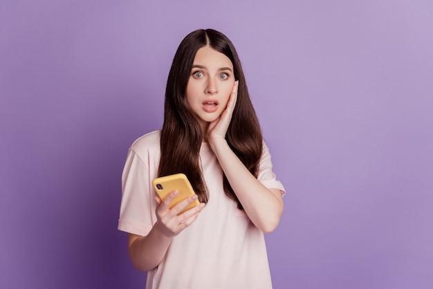 흥분한 귀여운 젊은 여성이 휴대폰을 만지는 얼굴을 들고 있는 사진