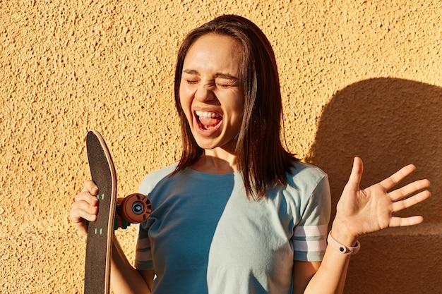 屋外の黄色い壁に立って、ロングボードを手に持って、幸せを表現して、幸せに叫んでいる青いtシャツを着ている興奮した黒髪の女性の写真。